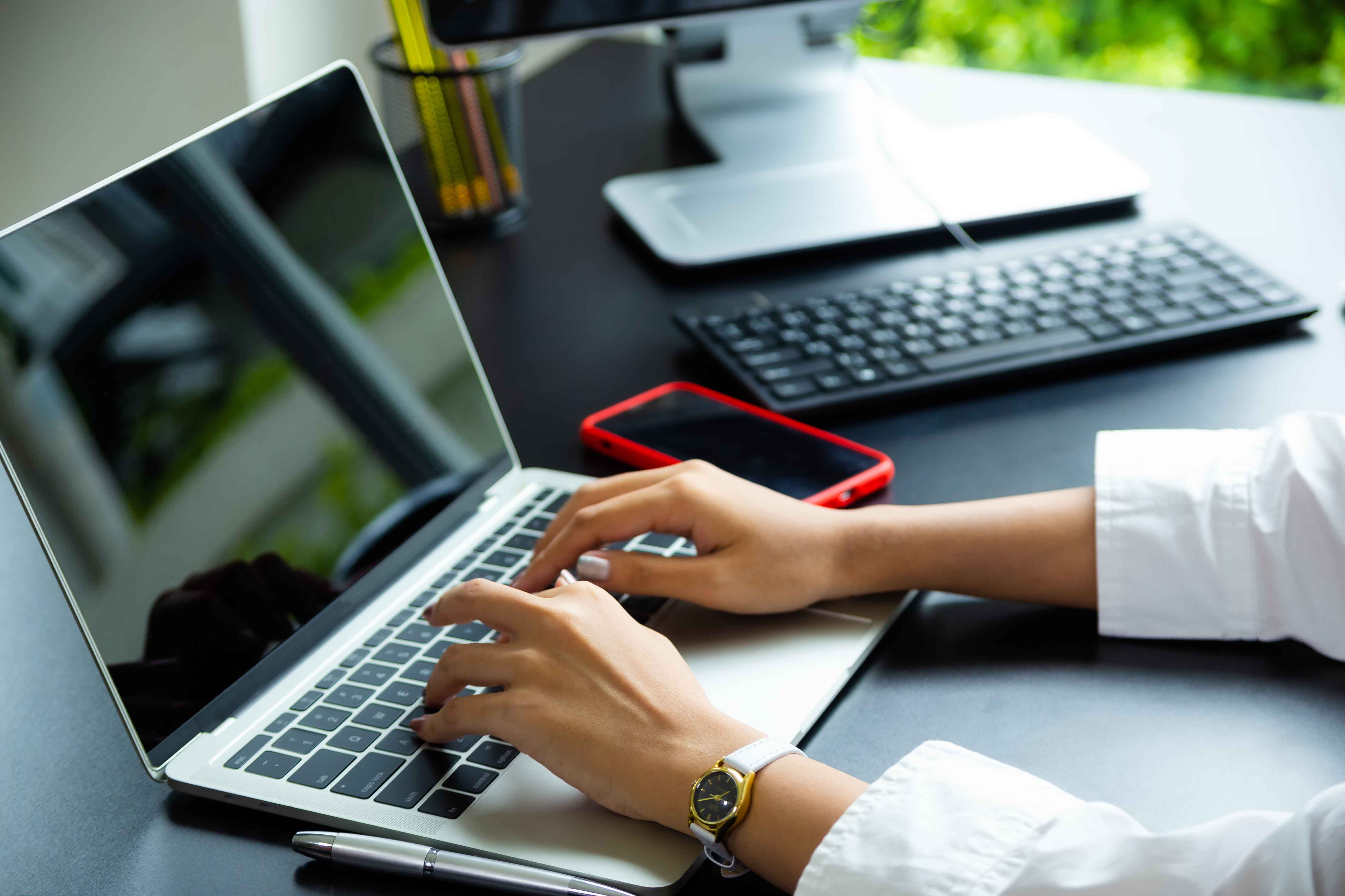 Close up hand of female typing on keyboard of laptop on table, working with technology device in modern office