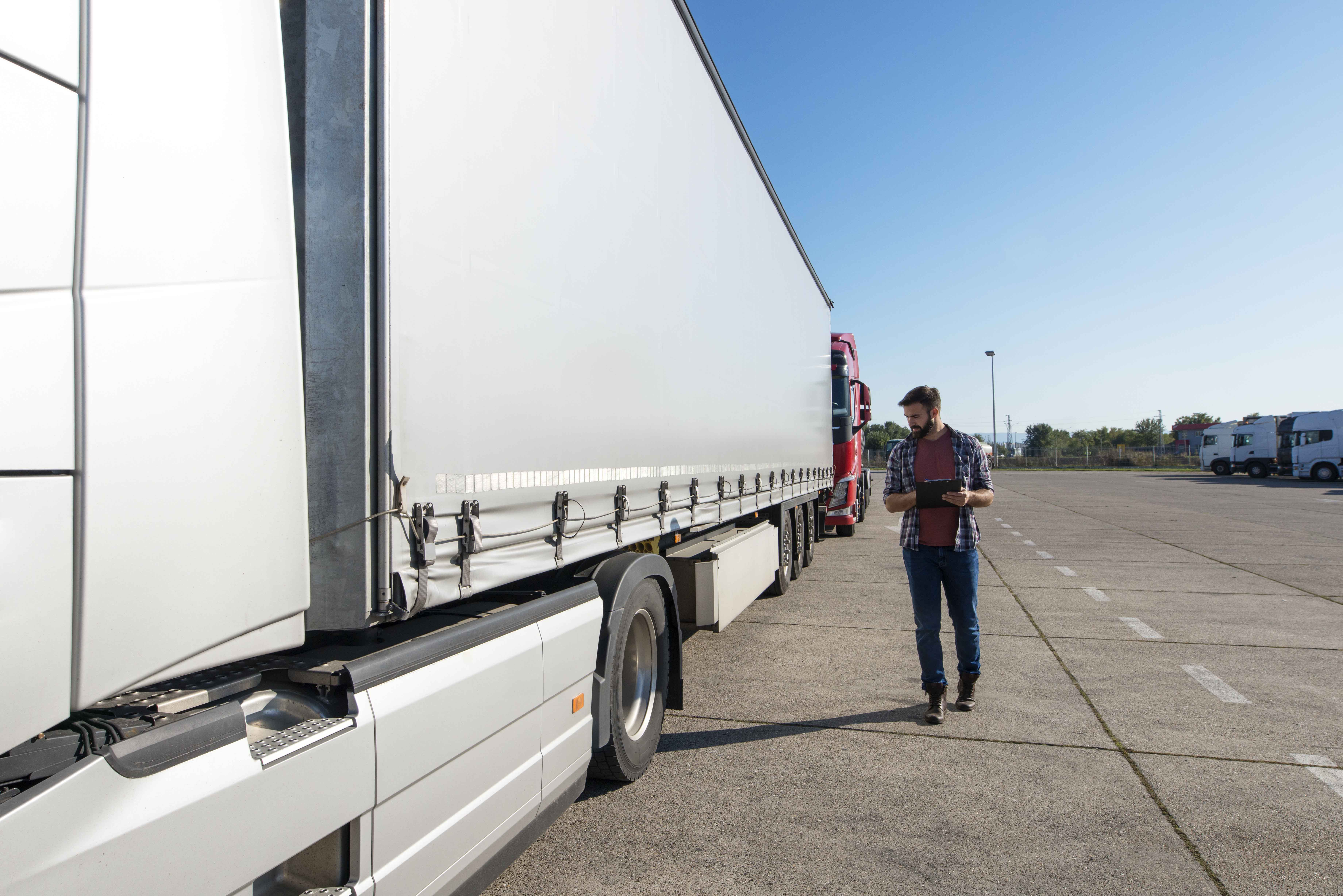 Truck driver inspecting vehicle, trailer and tires before driving.