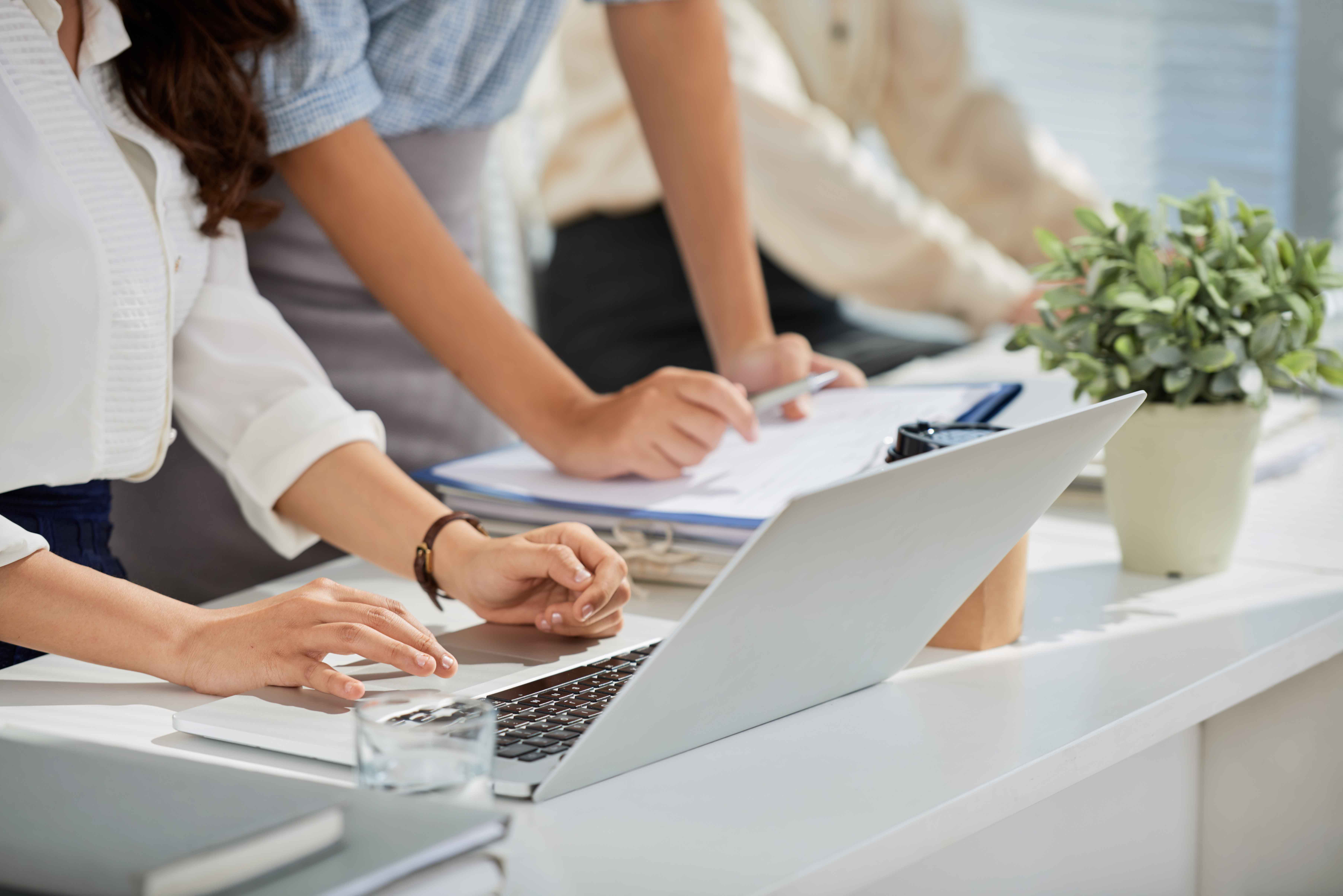 Cropped image of business ladies reading e-mails on laptop screen